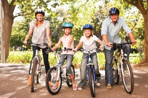 Happy family wearing helmets on a bicycle ride at the park together